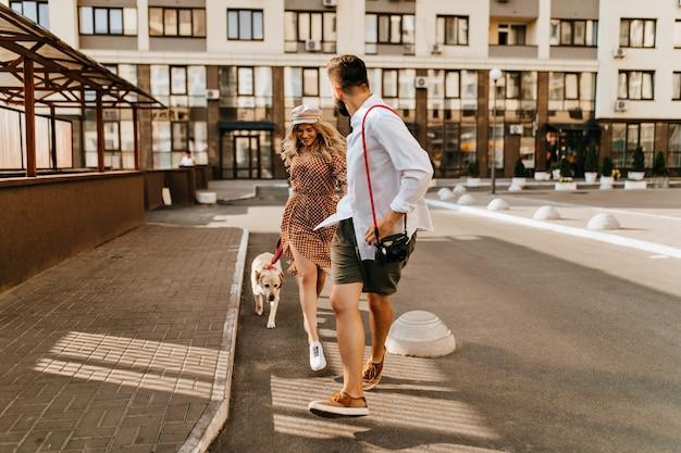 Stylowy mąż i żona w letnich strojach biegają i bawią się z psem na tle kamienicy. mężczyzna w lekkiej koszuli trzyma ukochaną dłoń i niesie aparat.