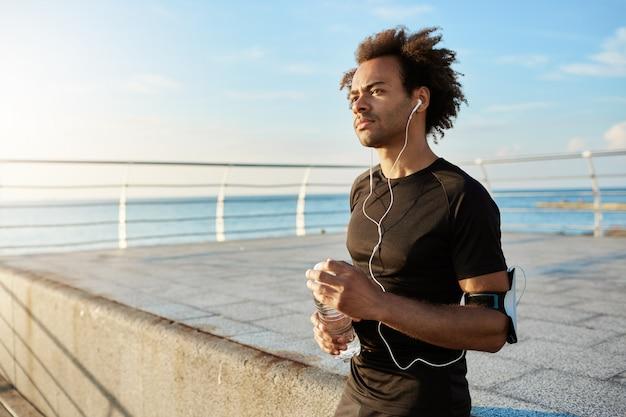 Stylowy męski jogger z krzaczastą fryzurą o poranku wyglądający prosto, lubiący zajęcia sportowe. wysportowany mężczyzna w słuchawkach z butelką wody w rękach robi sobie przerwę w środku treningu