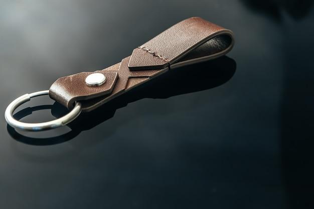 Stylowy męski metalowy brelok do kluczy na tle czarnego szkła