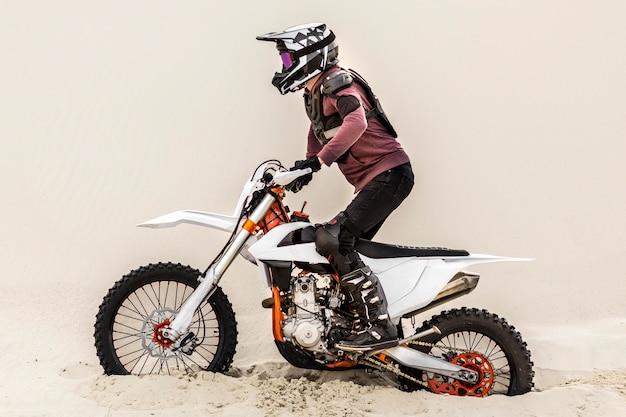 Stylowy mężczyzna jedzie motocyklem na pustyni
