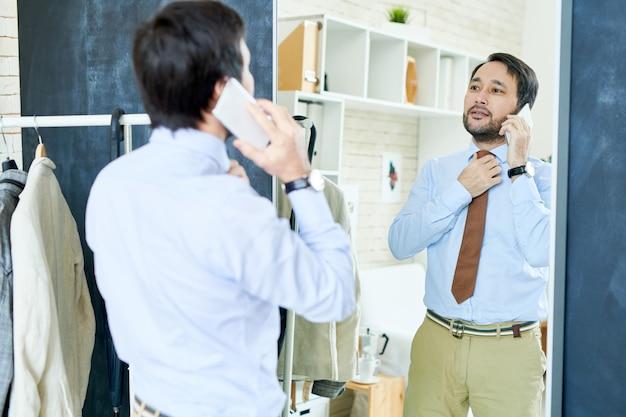 Stylowy mężczyzna mówi na telefon w pobliżu lustra