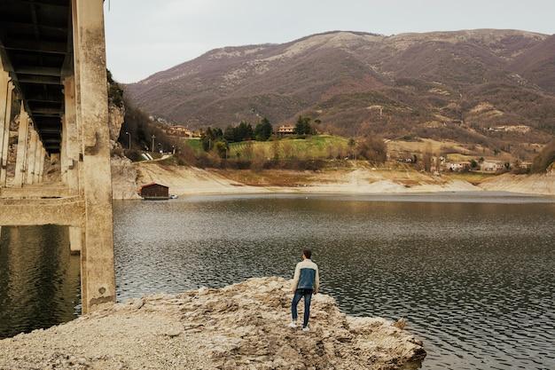 Stylowy mężczyzna ogląda wspaniałe krajobrazy w górach wiosną we włoszech.
