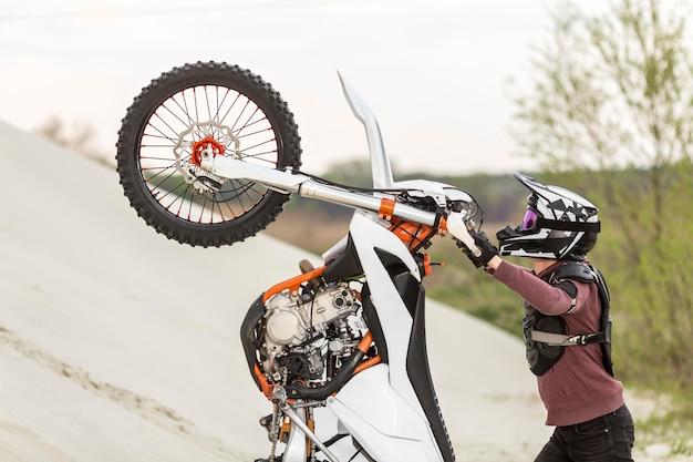 Stylowy mężczyzna podnoszenia motocykla na pustyni