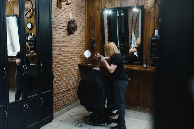 Stylowy mężczyzna siedzi fryzjer sklep fryzjerka fryzjer kobieta strzyżenia włosów