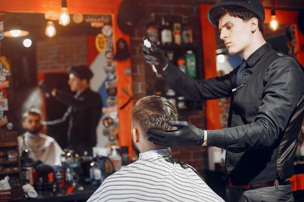 Stylowy mężczyzna siedzi w zakładzie fryzjerskim
