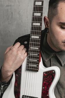 Stylowy mężczyzna trzyma gitarę elektryczną