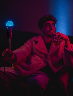 Stylowy mężczyzna trzyma lampę i szkło z napojem