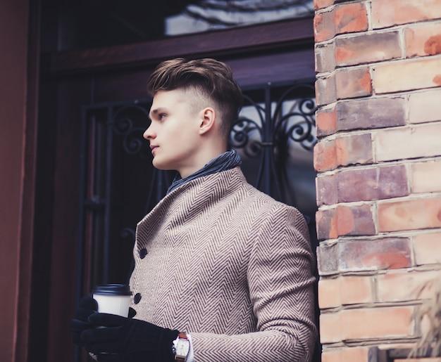 Stylowy mężczyzna ubrany w płaszcz stojący na ulicy i trzymając kawę na wynos