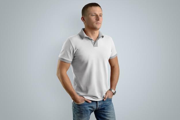 Stylowy mężczyzna w białej koszulce polo i niebieskich dżinsach z rękami w kieszeniach na białym tle na szarej ścianie, widok z przodu.