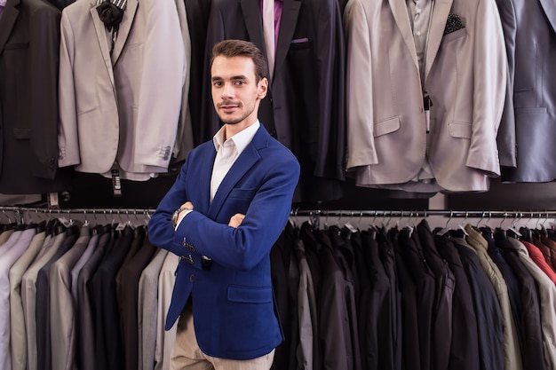Stylowy mężczyzna w butiku odzieżowym na tle kurtek