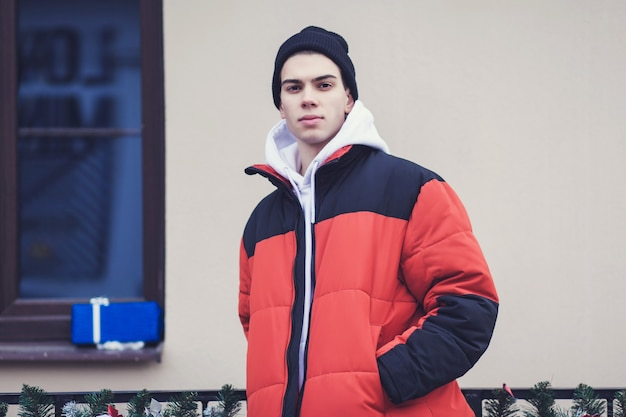 Stylowy mężczyzna w czarnej czapce i kurtce zimowej w mieście