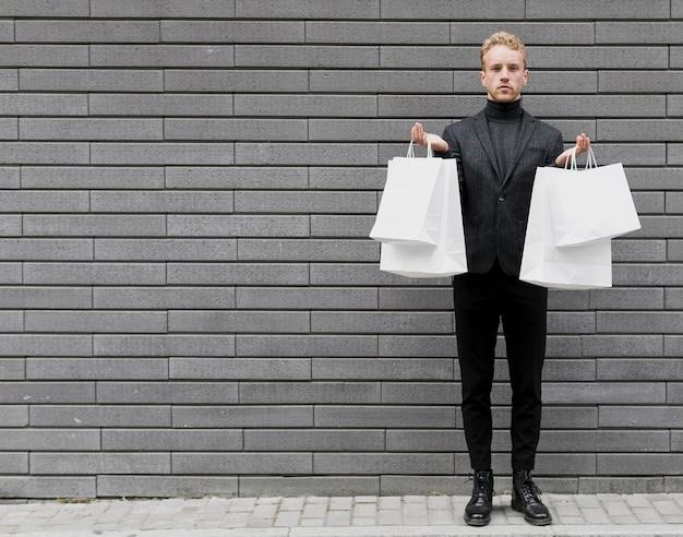 Stylowy mężczyzna w czerni z białymi torbami na zakupy
