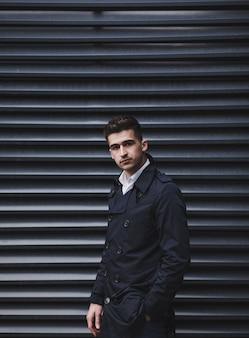 Stylowy mężczyzna w eleganckim płaszczu pozowanie w pobliżu ściany