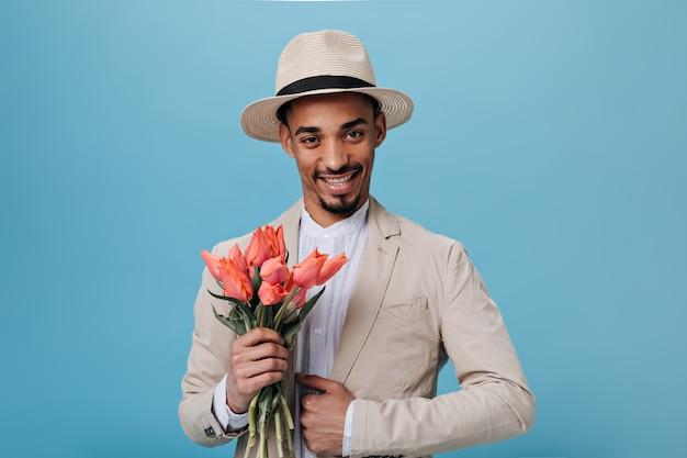 Stylowy mężczyzna w garniturze i kapeluszu trzymający bukiet na niebieskiej ścianie