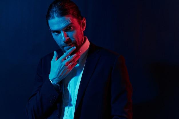 Stylowy mężczyzna w kurtce stwarzający pewność siebie na ciemnym tle