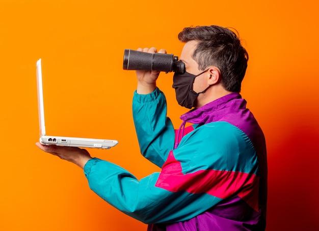 Stylowy mężczyzna w masce i dresie z lat 80., z laptopem i lornetką