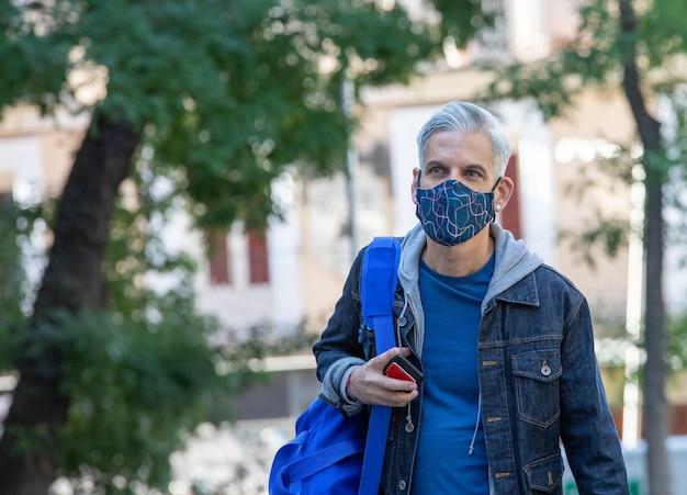 Stylowy mężczyzna w masce idąc ulicą