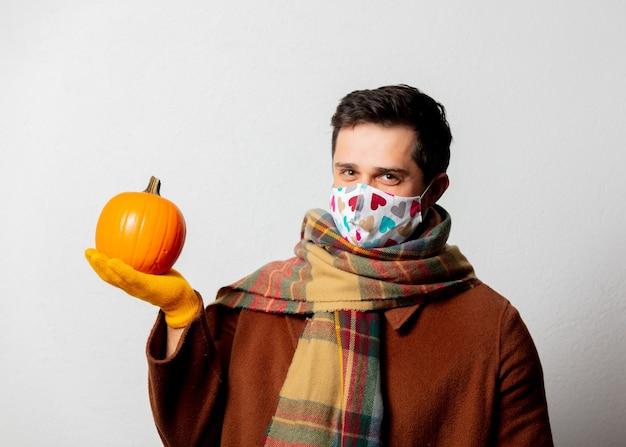 Stylowy mężczyzna w płaszczu i szaliku z dynią