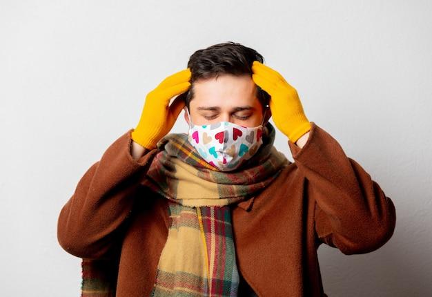 Stylowy mężczyzna w płaszczu i szaliku z maską