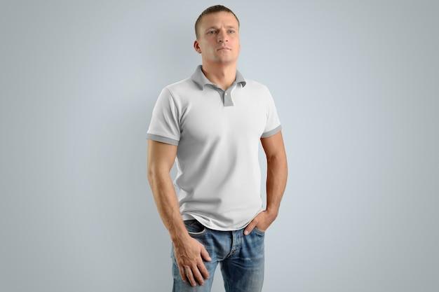 Stylowy mężczyzna w puste koszulka polo i niebieskie dżinsy na białym tle na szarej ścianie, widok z przodu.