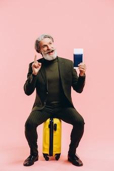 Stylowy mężczyzna w średnim wieku w garniturze siedzi na żółtej walizce i ma paszport.