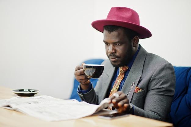 Stylowy mężczyzna w szarej marynarce i czerwonym kapeluszu pije kawę w kawiarni i czyta gazety