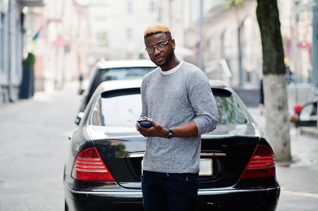Stylowy mężczyzna w szarym swetrze i okularach pozuje na ulicy przed czarnym samochodem służbowym i mówi przez telefon