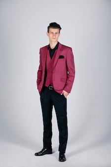 Stylowy mężczyzna w szkarłatnej kurtce na jasnym tle