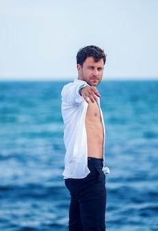 Stylowy mężczyzna wyciągający rękę nad brzegiem morza