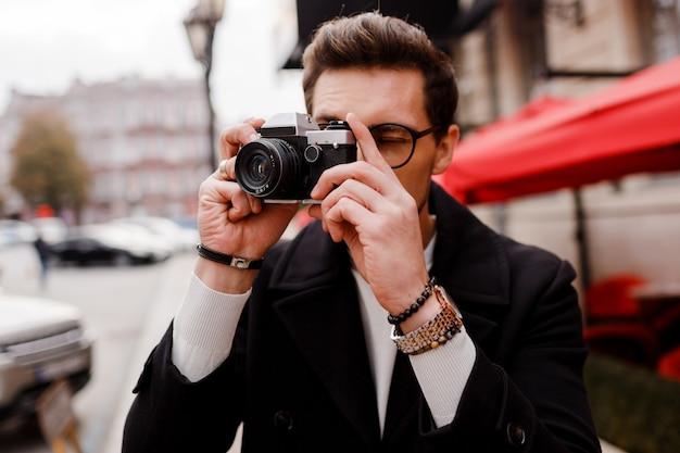 Stylowy mężczyzna z aparatem fotograficznym robiąc zdjęcia w europejskim mieście.