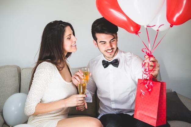 Stylowy mężczyzna z balonami i czerwona torba
