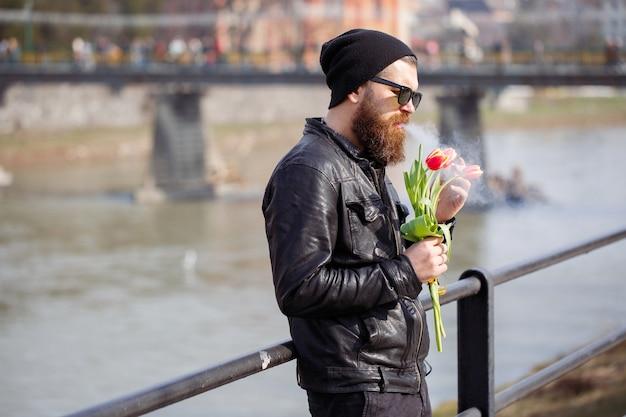 Stylowy mężczyzna z brodą w okularach przeciwsłonecznych z wąsami w ciepłej czapce i skórzanej kurtce trzyma bukiet czerwonych tulipanów i pali papierosa