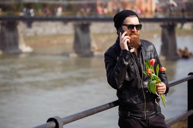 Stylowy mężczyzna z długą brodą i wąsami w czarnej ciepłej czapce i skórzanej kurtce trzymający bukiet czerwonych tulipanów i uśmiechnięty rozmawia przez telefon