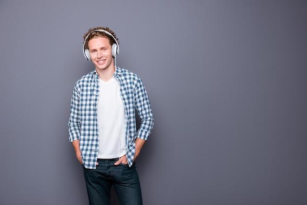 Stylowy mężczyzna z falowanymi włosami w kraciastej koszuli, słuchając muzyki w słuchawkach