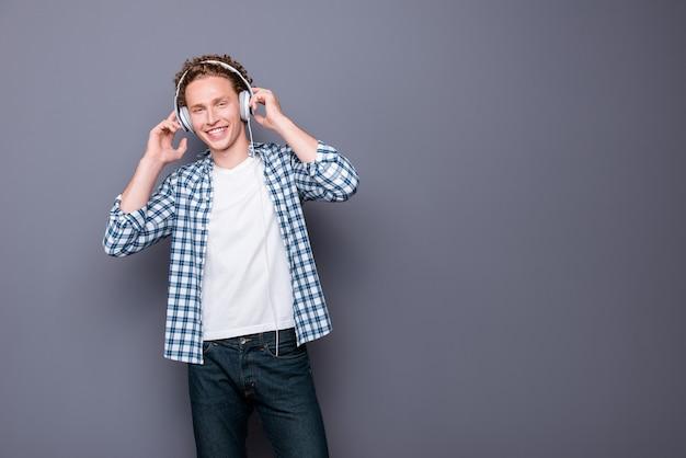 Stylowy mężczyzna z falowanymi włosami w swobodnej kraciastej koszuli, słuchając muzyki