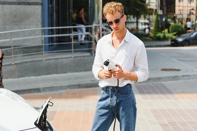 Stylowy mężczyzna z filiżanką kawy w ręku wkłada wtyczkę do gniazda ładowania samochodu elektrycznego