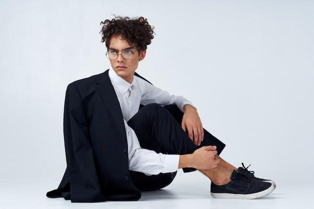 Stylowy mężczyzna z kręconymi włosami w trampki na jasnym tle kurtka na modelu spodnie na ramię