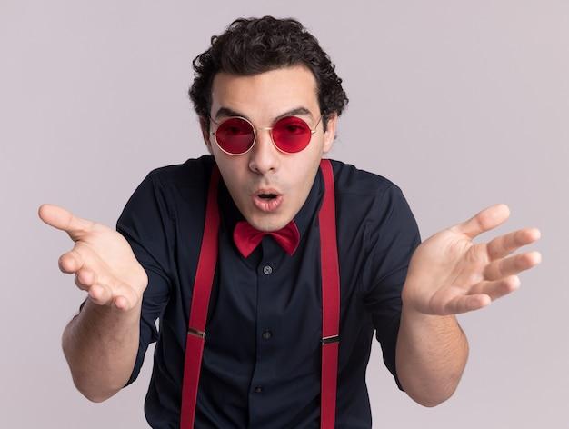 Stylowy mężczyzna z muszką w okularach i na szelkach patrząc na przód zdezorientowany i zaskoczony z podniesionymi rękami stojącymi nad białą ścianą