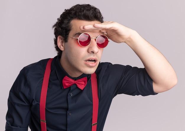 Stylowy mężczyzna z muszką w okularach i szelkach, patrząc daleko z ręką nad głową, stojąc na białej ścianie