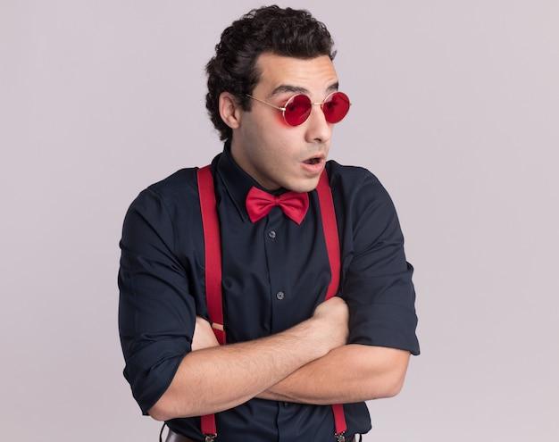 Stylowy mężczyzna z muszką w okularach i szelkach patrząc na bok zaskoczony ze skrzyżowanymi rękami stojąc na białej ścianie