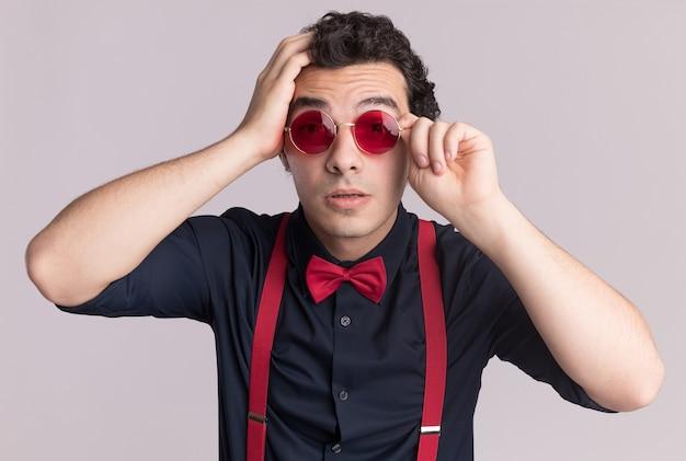 Stylowy mężczyzna z muszką w okularach i szelkach patrząc z przodu szczęśliwy i zdziwiony stojąc nad białą ścianą