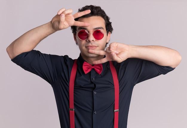 Stylowy mężczyzna z muszką w okularach i szelkach patrząc z przodu z uśmiechem na twarzy przedstawiający znak v stojący nad białą ścianą