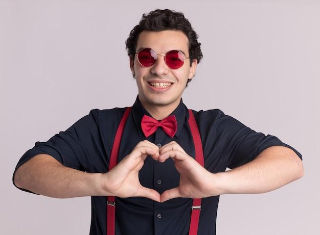 Stylowy mężczyzna z muszką w okularach i szelkach robi gest serca palcami uśmiechnięty wesoło stojąc na białej ścianie