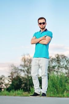 Stylowy mężczyzna ze skrzyżowanymi rękami na sobie niebieski polo na pustej drodze