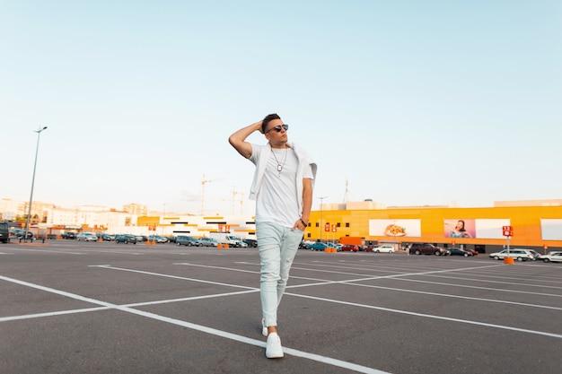 Stylowy miejski młody mężczyzna w okularach przeciwsłonecznych w modnych letnich ubraniach w skórzanych białych modnych trampkach lubi spacer po mieście. modny facet ze stylową fryzurą na odkrytym parkingu.