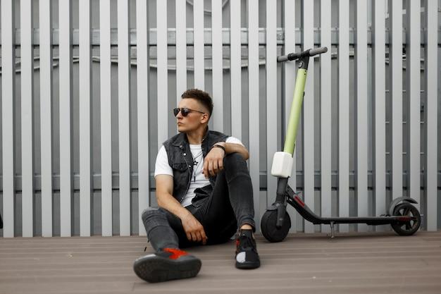 Stylowy, miły młody hipster mężczyzna w ciemnych okularach przeciwsłonecznych w modnych letnich ubraniach odpoczywa po jeździe na skuterze elektrycznym