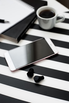 Stylowy minimalistyczny obszar roboczy z makiety smartphone, ołówek, filiżankę kawy, bezprzewodowy ea