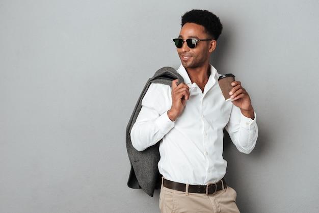 Stylowy młody afro amerykański mężczyzna trzyma kurtkę na ramieniu