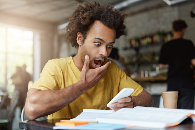 Stylowy młody afroamerykański student z kolczykiem ubrany w żółtą koszulkę z zaskoczonym wyrazem twarzy
