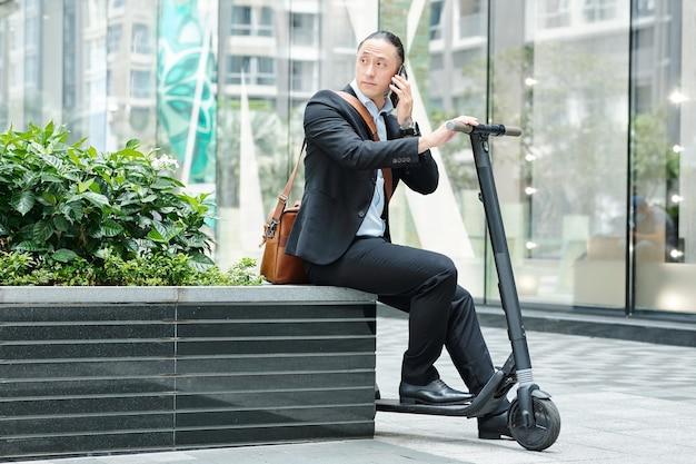Stylowy młody biznesmen siedzi na ławce ze skuterem, rozmawia przez telefon i odwraca wzrok